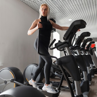 운동화에 검은 색 세련된 옷을 입은 젊은 아름 다운 스포티 한 여자는 체육관에서 시뮬레이터에서 심장 훈련을합니다.