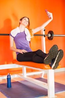 체육관에서 스마트 폰에 셀카 사진을 만드는 젊은 아름 다운 스포티 한 여자-그녀의 어깨에 수건으로 앉아 체육관에서 셀카를 마시는 웃는 백인 sportswoman.
