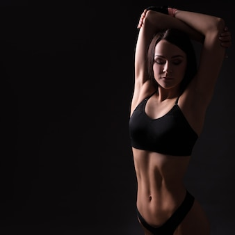Young beautiful sporty woman in sexy sportswear posing over black background with copy space