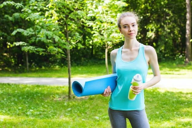公園で水とジムのマットのボトルを持つ若い美しいスポーティな女性。
