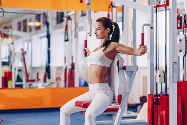 Young beautiful sporty woman with perfect body doing workouts in a gym