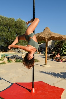 Young beautiful strong woman making a pose on a pole.