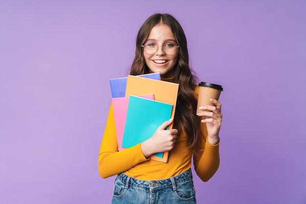 Молодая красивая студентка в очках держит тетрадь и изолированную чашку кофе