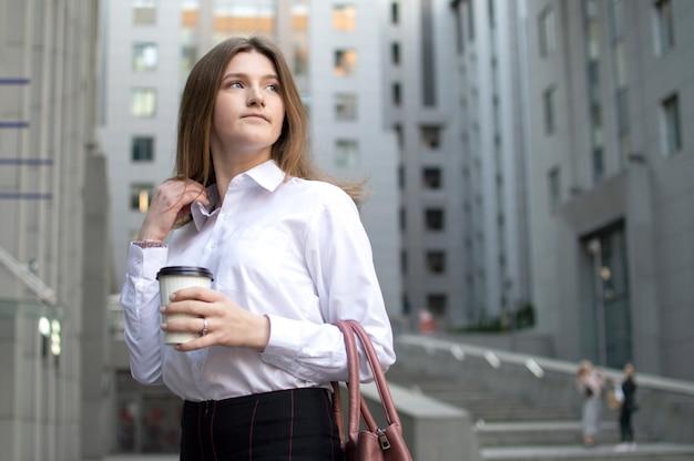 Молодая красивая студентка стоит с кофе