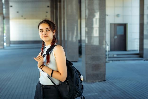 Молодой красивый студент с рюкзаком на плече идет в школу, крупный план. школьница с двумя косами стоит перед колледжем