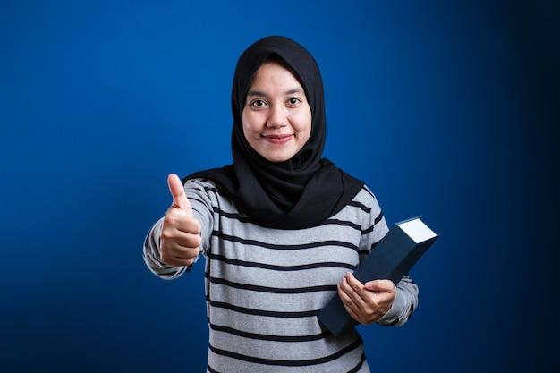 手で幸せな親指を立てるジェスチャーをしている本を持っているイスラム教徒のヒジャーブを身に着けている若い美しい学生女性。成功を示しているカメラを見て表現を承認します。