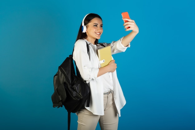 Young beautiful student woman with backpack and headphones holding yellow notepad and makes selfie on blue