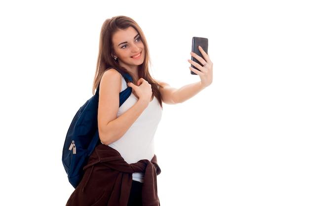 バックパックを持つ若い美しい学生女性は、スタジオで白い壁に自分撮りを分離します