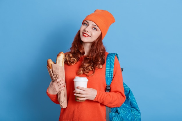 Young beautiful student woman with rucksack on back and coffee to go