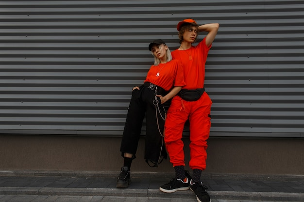 Молодые красивые стильные пары моделей в модных кепках и модной оранжевой одежде стоят у серой стены