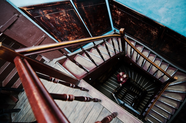 Young beautiful stylish couple in a red dress in big wooden vintage stairs