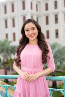 도시 사이를 걷고 포즈를 취하는 핑크색 드레스를 입은 젊고 세련된 소녀