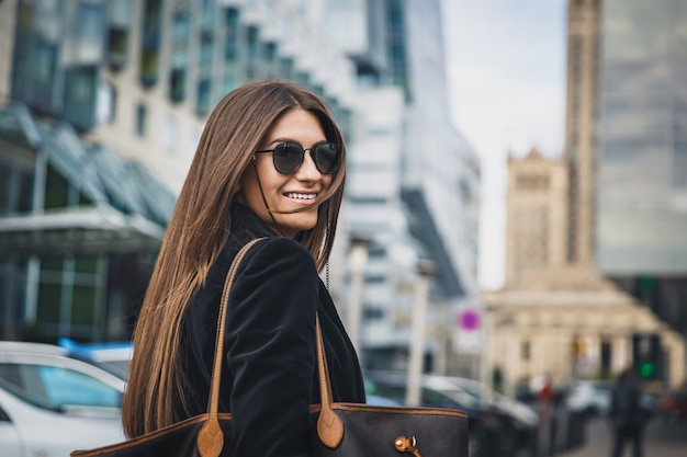 Young beautiful stylish girl in sunglasses walking on street. close up portrait of woman is turn around at camera and smiles.
