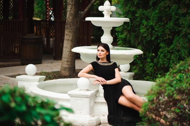 ウォーキングや噴水の近くの街で短い黒のドレスでポーズ美しいスタイリッシュな少女。上品な若い女性の夏の屋外の肖像画。
