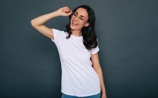 白いtシャツと眼鏡の若い美しいスタイリッシュな幸せな女性が灰色の背景にポーズをとっています Premium写真