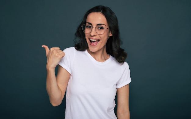 白いtシャツを着た若い美しいスタイリッシュな幸せな女性がポーズをとって灰色の背景を指しています