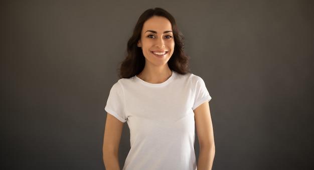 白いtシャツの若い美しいスタイリッシュな幸せな女性は灰色の背景にポーズをとっています