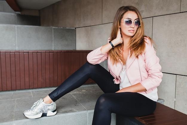 ピンクの革のジャケットの若い美しいスタイリッシュな流行に敏感な女性
