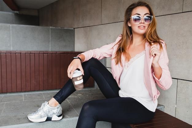 Giovane bella donna alla moda hipster in giacca di pelle rosa