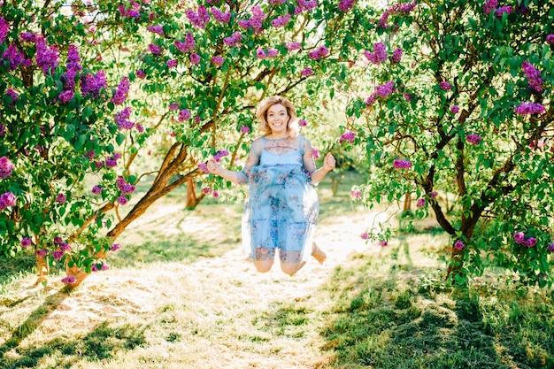 Молодая красивая стильная модель девушка в платье повеселиться на открытом воздухе в сиреневый цветущий сад в летний день.