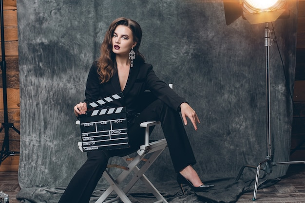 Young beautiful stylish sexy woman on cinema backstage, holding movie clapper