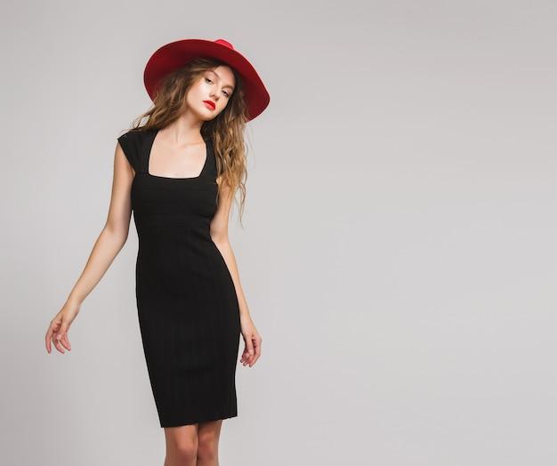 Giovane bella donna alla moda in vestito nero, cappello rosso, rossetto rosso, felice, sorridente, sexy, elegante