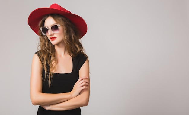 Young beautiful stylish woman in black dress, red hat, sunglasses, red lipstick, happy, smiling, sexy, elegant