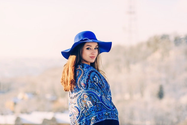 Young beautiful stylish woman in blue hat and scarf walking in the park