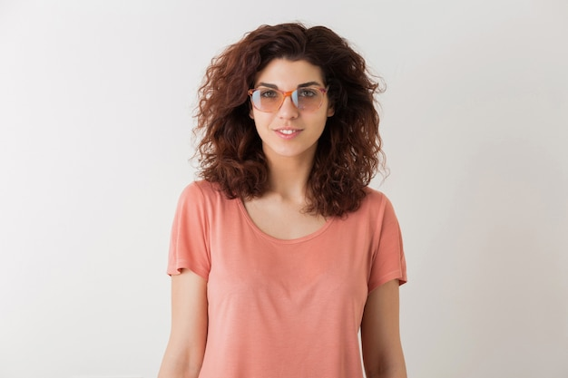 Young beautiful stylish woman in glasses, curly hair, smiling, positive emotion, happy, isolated on white background, pink t-shirt, hipster style, student, looking in camera, natural look