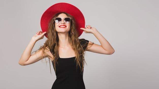 Молодая красивая стильная женщина в черном платье, красной шляпе, солнцезащитных очках, красной помаде, счастливой, улыбающейся, сексуальной, элегантной