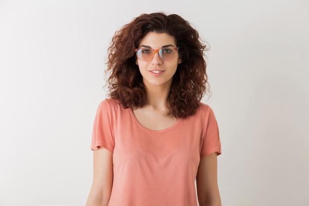 メガネ、巻き毛、笑顔、肯定的な感情、幸せ、白い背景で隔離の若い美しいスタイリッシュな女性、ピンクのtシャツ、流行に敏感なスタイル、学生、カメラで探して、自然な表情
