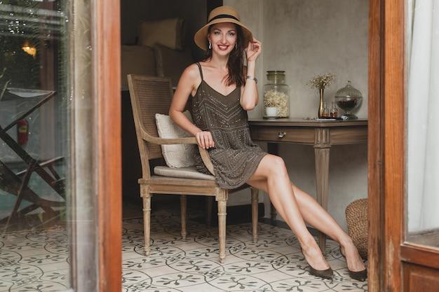 Молодая красивая стильная женщина в номере курортного отеля, сидя за столом, в модном платье, в стиле сафари, соломенной шляпе, улыбается, счастлива, летние каникулы, богемный наряд