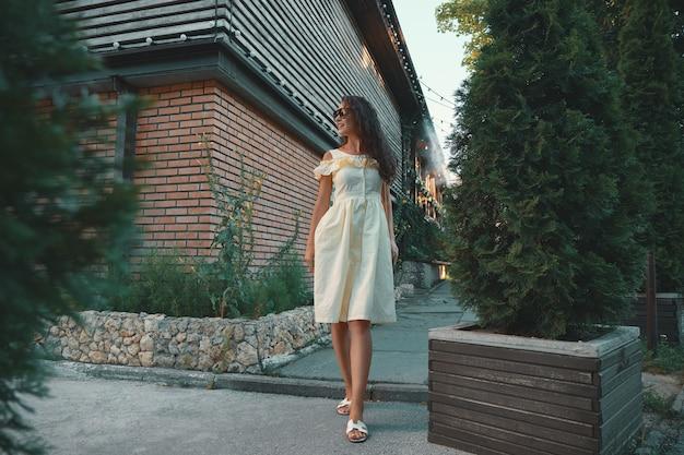 Молодая красивая стильная женщина в солнцезащитных очках, идущая на летнем платье