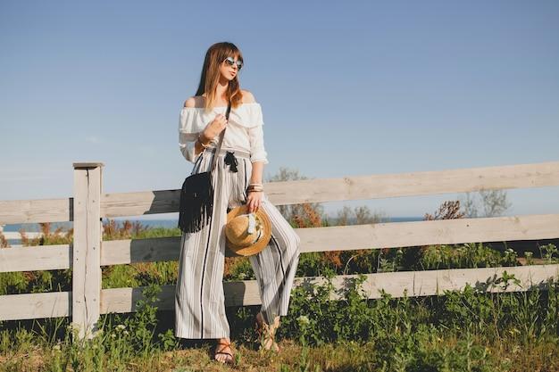 屋外でポーズをとる若い美しいスタイリッシュな女性