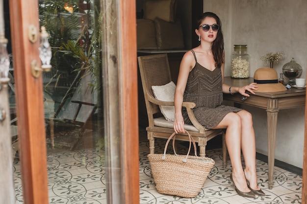 Giovane bella donna alla moda nella camera d'albergo del resort, seduta al tavolo, indossando abiti alla moda, stile safari, cappello di paglia, sorridente, felice, vacanze estive, vestito bohémien, borsa da spiaggia, occhiali da sole, gambe