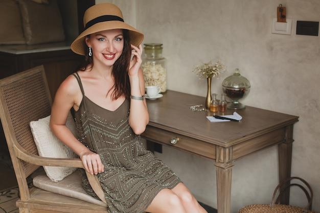 Giovane bella donna elegante nella camera d'albergo del resort, seduto al tavolo, indossando abiti alla moda, stile safari, cappello di paglia, sorridente, felice, vacanze estive, vestito bohémien