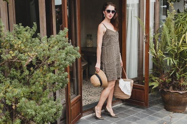 Giovane bella donna elegante in hotel resort, indossando abiti alla moda, stile safari, cappello di paglia, vacanze estive, abito bohémien, borsa da spiaggia, occhiali da sole