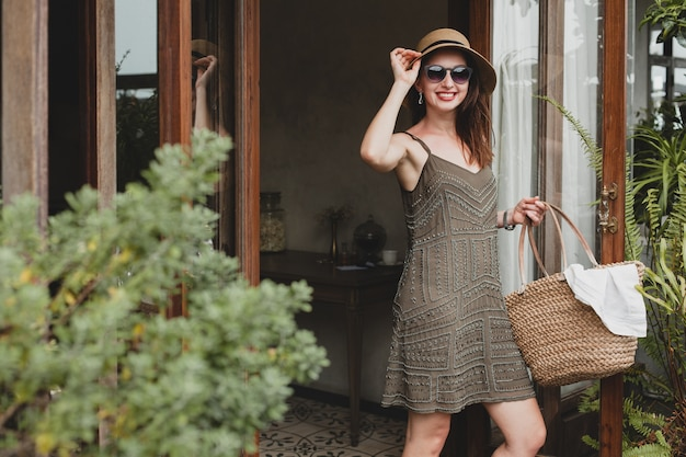 Young beautiful stylish woman in resort hotel, wearing trendy dress, safari style, straw hat, summer vacation, bohemian outfit, beach bag, sunglasses