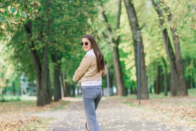 가을 공원으로 전기 스쿠터를 타고 젊은 아름 다운 세련 된 여자