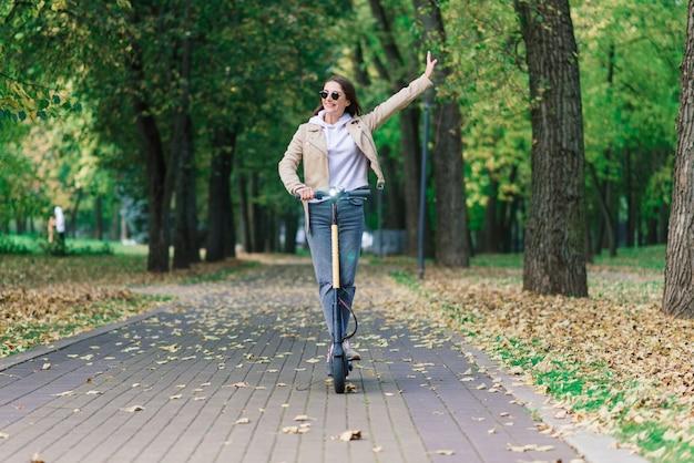 전기 scooter를 타고 젊은 아름 다운 세련 된 여자