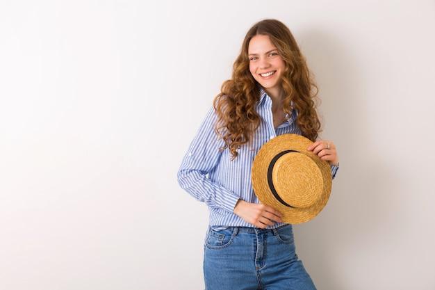 Giovane bella donna alla moda in vestito di stile di estate che posa sul cappello di paglia della tenuta della parete bianca