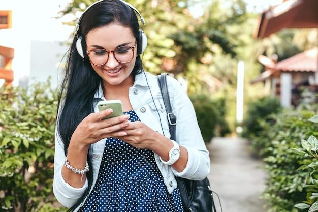 スマートフォン、ヘッドフォン、眼鏡、夏、ヴィンテージデニムの服、笑顔、幸せ、ポジティブを使用して若い美しいスタイリッシュな女性