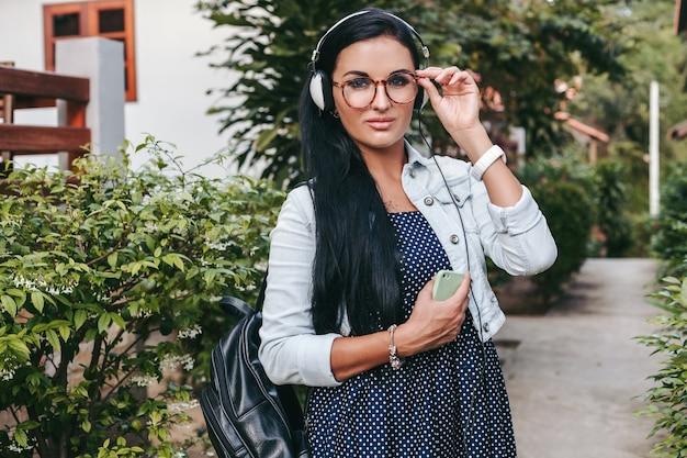 Молодая красивая стильная женщина, использующая смартфон, наушники, очки, лето, винтажный джинсовый наряд, улыбающаяся, счастливая, позитивная