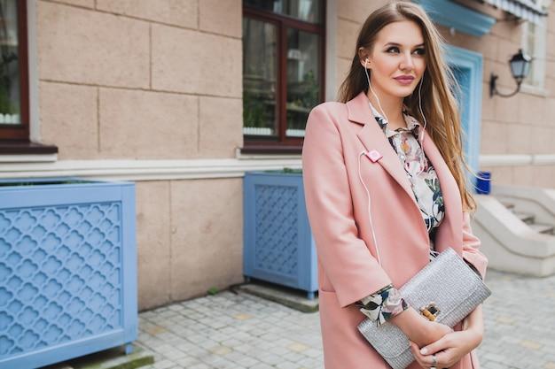 ピンクのコートで通りを歩いて、財布を手で押し、音楽を聴く若い美しいスタイリッシュな女性