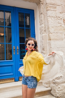 Young beautiful stylish woman walking in old city street