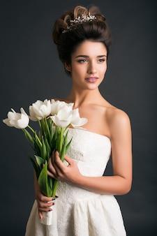 Giovane bella donna alla moda in abito da sposa