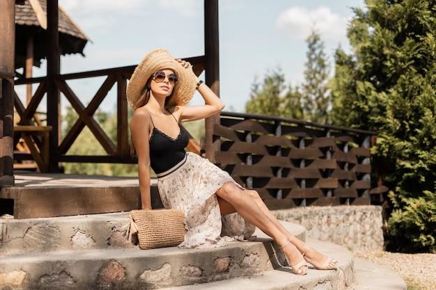 麦わら帽子とレースのランジェリーとヴィンテージドレスのファッショナブルなニットのハンドバッグを持つ若い美しいスタイリッシュな女性は、夏休みの自然の階段に座っています
