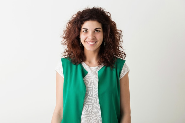 Молодая красивая стильная женщина с естественной вьющейся прической улыбается, положительные эмоции, счастливая, изолированная на белом фоне, тренд летней моды, стиль хипстера, смотрит в камеру, зеленый жилет