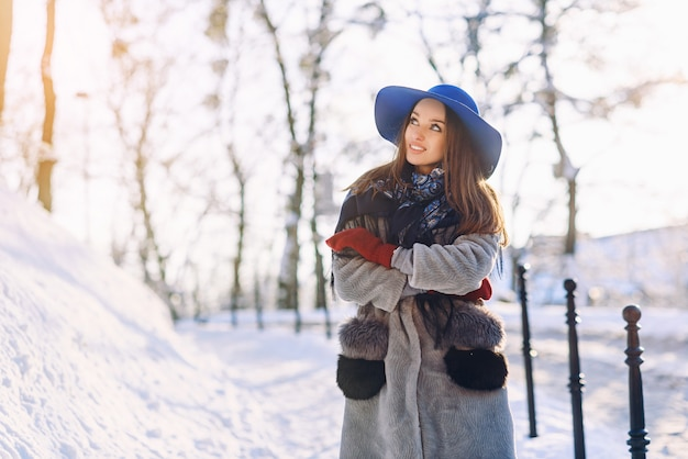 Young beautiful stylish woman with perfect smile in blue hat and scarf walking down the street