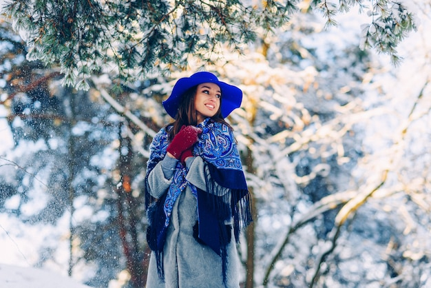 Young beautiful stylish woman with perfect smile in blue hat and scarf walking in the park